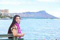 Adolescente hawaiano con los leus que se sientan por el océano, Waikiki en fondo Imagen de archivo