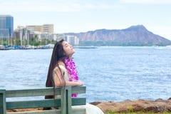 Adolescente hawaiano con los leus que se sientan por el océano, Waikiki en fondo Fotos de archivo libres de regalías