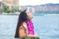Adolescente hawaiano con los leus que se sientan por el océano, Waikiki en fondo Imagenes de archivo