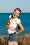 Adolescente hermoso alegre cerca del mar. Foto de archivo