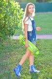 Adolescente hermoso con el monopatín en el parque verde en verano Imagenes de archivo