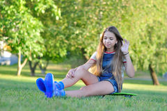 Adolescente hermoso con el monopatín en el parque verde en verano Fotos de archivo