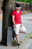 Adolescente hermoso con el monopatín que se coloca en la calle Fotografía de archivo
