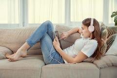 Adolescente hermoso con el ordenador de la PC de la tableta y la música que escucha de los auriculares Foto de archivo libre de regalías