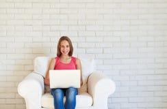 Adolescente hermoso con el ordenador portátil abierto en el agai blanco de la butaca Imagen de archivo