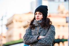 Adolescente hermoso con el sombrero negro y esperar gris de la capa Foto de archivo libre de regalías