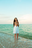 Adolescente hermoso con la cáscara en la playa de la tarde Imagenes de archivo