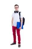 Adolescente hermoso con la mochila y los auriculares aislados en wh Imagen de archivo libre de regalías