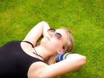 Adolescente hermoso con las gafas de sol que mienten en ella detrás en Fotos de archivo libres de regalías