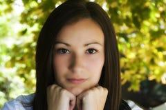 Adolescente hermoso con las hojas en el fondo Fotografía de archivo