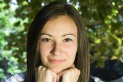 Adolescente hermoso con las hojas en el fondo Foto de archivo libre de regalías