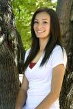 Adolescente hermoso con las hojas en el fondo Foto de archivo