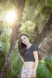 Adolescente hermoso con las palmeras y el sol Foto de archivo libre de regalías