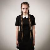 Adolescente hermoso con las trenzas vestidas en negro Fotos de archivo libres de regalías