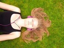 Adolescente hermoso con los auriculares que mienten en ella detrás Fotografía de archivo