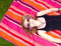 Adolescente hermoso con los auriculares que mienten en ella detrás Imágenes de archivo libres de regalías