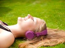 Adolescente hermoso con los auriculares que mienten en ella detrás Foto de archivo