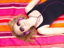 Adolescente hermoso con los auriculares que mienten en ella detrás Imagen de archivo