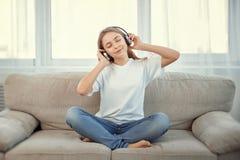 Adolescente hermoso con música que escucha del smartphone y de los auriculares Fotografía de archivo libre de regalías