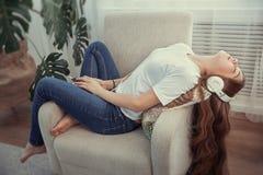 Adolescente hermoso con música que escucha del smartphone y de los auriculares Imagenes de archivo