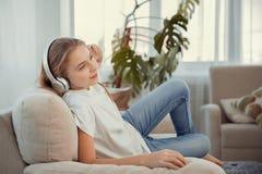 Adolescente hermoso con música que escucha del smartphone y de los auriculares Foto de archivo