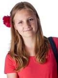 Adolescente hermoso con una flor en su pelo que mira en el th Foto de archivo
