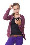 Adolescente hermoso confuso con el teléfono móvil, aislado encendido Fotos de archivo