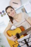 Adolescente hermoso de la muchacha en la camisa y los vaqueros rasgados que tocan la guitarra Imagen de archivo
