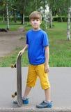 Adolescente hermoso del muchacho con el monopatín Imagen de archivo libre de regalías