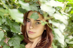 Adolescente hermoso detrás del follaje Imagenes de archivo