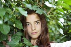 Adolescente hermoso detrás del follaje Fotografía de archivo