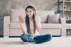 Adolescente hermoso emocionado está escuchando la música en earpho blanco grande Foto de archivo libre de regalías