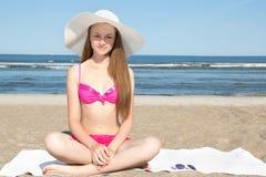 Adolescente hermoso en bikini rosado y el sombrero blanco que se sientan en el b Fotos de archivo libres de regalías