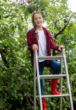 Adolescente hermoso en camisa a cuadros y las botas de goma que suben en la escalera de mano en la huerta Foto de archivo