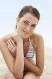 Adolescente hermoso en el bikini que se sienta en la playa Imagen de archivo libre de regalías