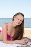Adolescente hermoso en el bikini rosado que miente en la playa Foto de archivo