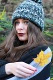 Adolescente hermoso en el otoño que sostiene una hoja Foto de archivo libre de regalías