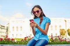 Adolescente hermoso en las gafas de sol rosadas que se sientan en el macizo de flores a Foto de archivo libre de regalías