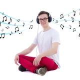 Adolescente hermoso en música que escucha de los auriculares aislado en w Fotografía de archivo