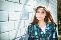 Adolescente hermoso en sombrero cerca de la pared azul Fotografía de archivo