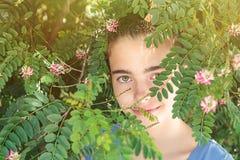Adolescente hermoso en un arbusto floreciente Foto de archivo libre de regalías