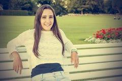 Adolescente hermoso en un banco Fotos de archivo