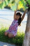 Adolescente hermoso en vestido rosado con el pelo largo en un parque verde del verano Foto de archivo
