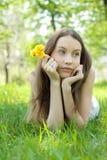 Adolescente hermoso joven con el césped del diente de león Foto de archivo libre de regalías