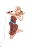 Adolescente hermoso joven feliz que salta y que canta con el micr Imagen de archivo libre de regalías