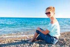 Adolescente hermoso joven realxing en pebbl del mar Mediterráneo Foto de archivo