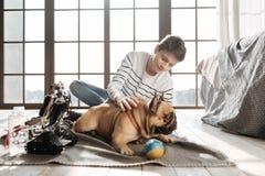 Adolescente hermoso mientras que juega así como su perro Foto de archivo libre de regalías
