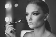 Adolescente hermoso que aplica el polvo cosmético en cara con la borla, concepto del cuidado de piel Fotografía de archivo