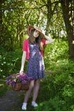 Adolescente hermoso que camina en bosque con una cesta de flores Imágenes de archivo libres de regalías