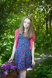Adolescente hermoso que camina en bosque con una cesta de flores Imagen de archivo libre de regalías